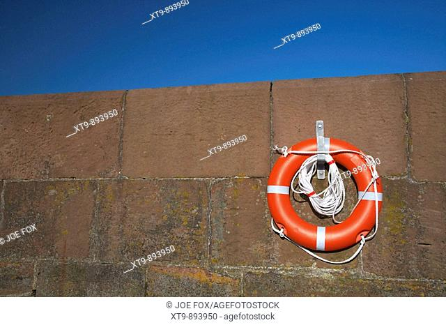 brand new bright red lifebelt with white rope hanging on a hanger on brown harbour wall with blue sky