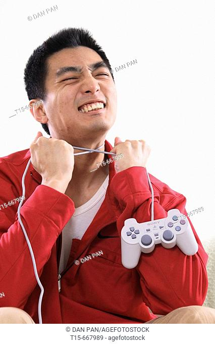 Asian man in his 20's using playstation game controller to strangle himself in frustration