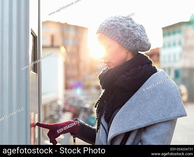 Casual woman buying public transport tickets on city urban vedning machine on cold winter day in Ljubljana, Slovenia