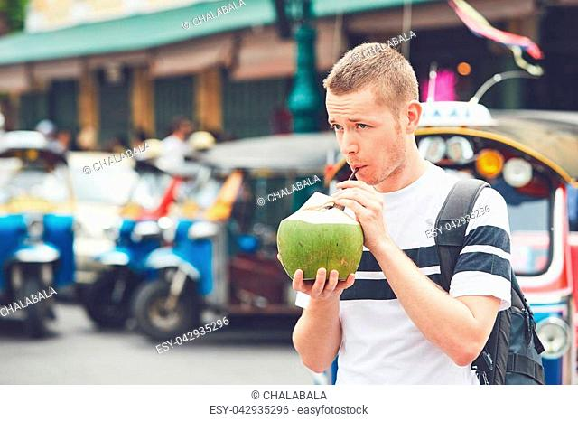Young man drinking coconut drink against tuk tuk taxi. Tourist on the street in Bangkok, Thailand