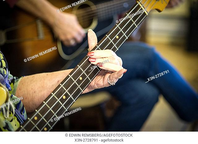 Elderly woman's hands on the fretboard of a bass guitar