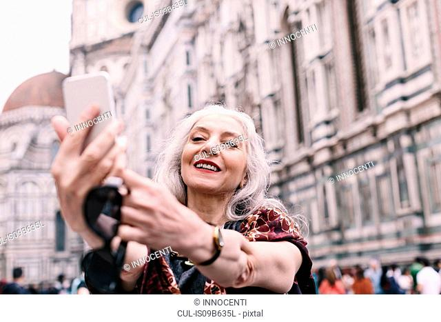 Stylish mature woman taking smartphone selfie in Florence, Italy