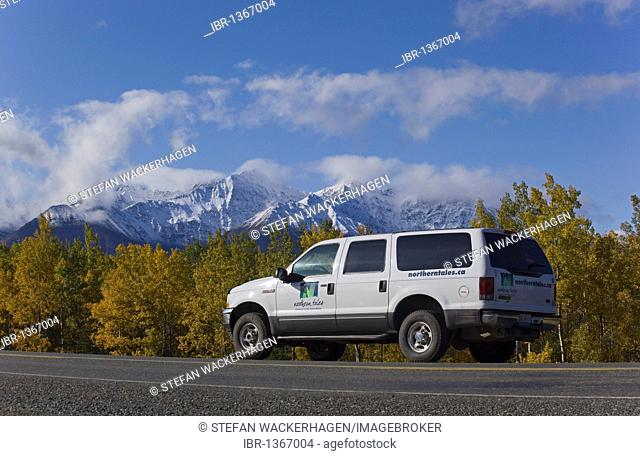 SUV driving along Alaska Highway, Indian Summer, leaves in fall colours, St. Elias Mountains behind, Kluane National Park and Reserve, Yukon Territory, Canada