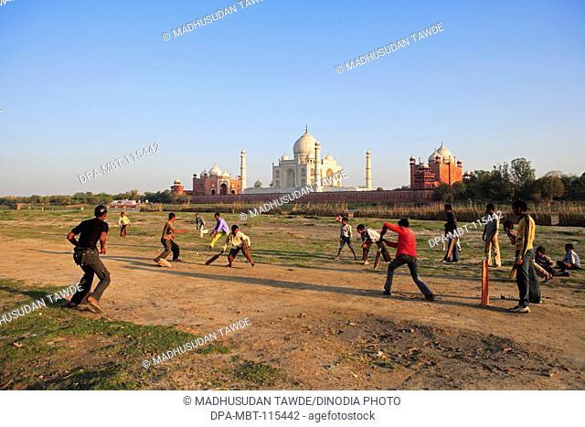 Children playing cricket at Taj Mahal Seventh Wonders of World on south bank of Yamuna river , Agra , Uttar Pradesh , India UNESCO World Heritage Site