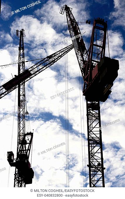 Three tower cranes silhouetted against a cloud filled sky