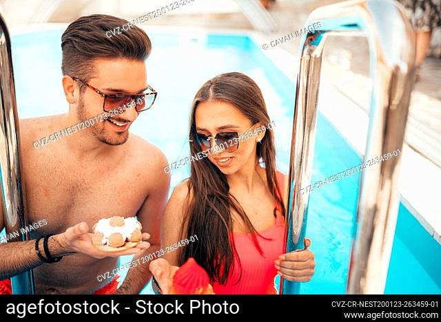 Young beautiful couple eating cookies by the pool