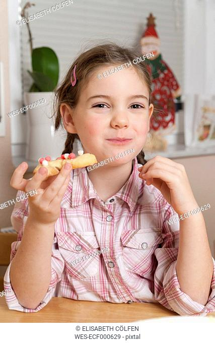 Portrait of little girl eating Christmas cookie