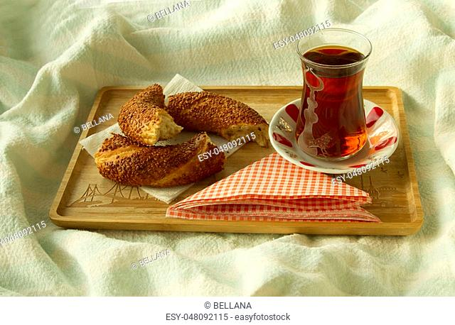 Bagel and cup of turkish tea on the wood tray with Istanbul picture on the bedcover, breakfast in bed