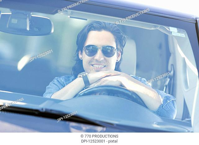 Young man sitting in the driver's seat of a vehicle posing for a picture while looking out the windshield; Edmonton, Alberta, Canada