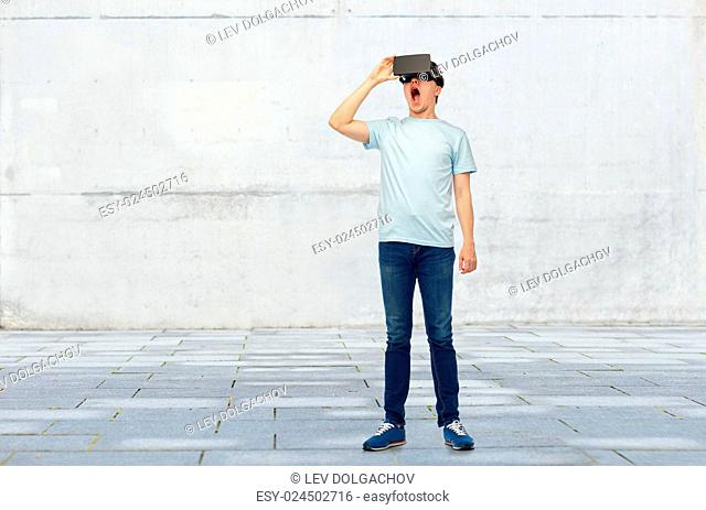 3d technology, virtual reality, entertainment, cyberspace and people concept - amazed young man with virtual reality headset or 3d glasses over street...