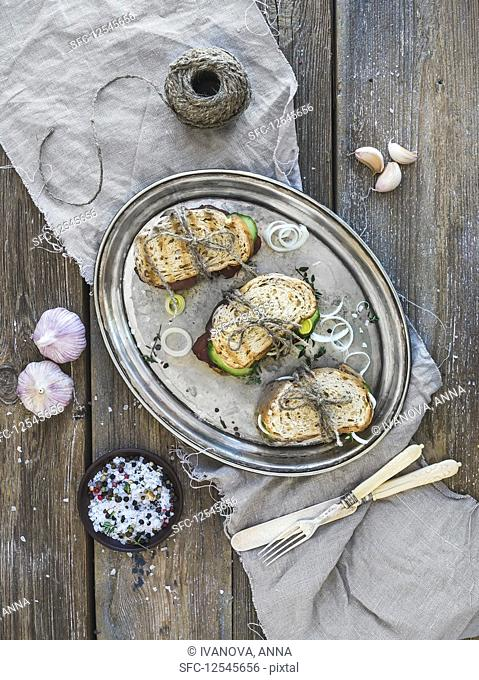 Sandwiches with smoked meat, cucumber, onion, herbs and spices on a metal dish over rough wood background