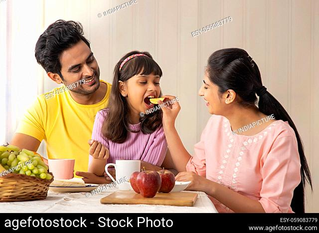 A HAPPY MOTHER FEEDING HER DAUGHTER WITH HUSBAND SITTING NEAR