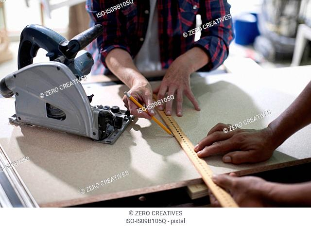 Cropped shot of carpenters marking measurements in furniture making workshop