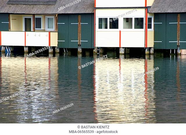 Photography of houses with boat shed at a lake