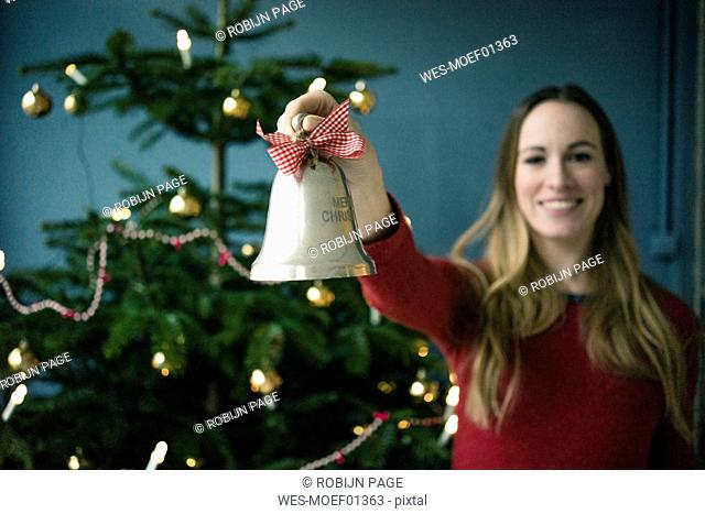 Smiling woman showing silver  Christmas bell