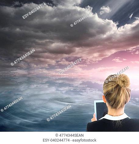 Composite image of blonde businesswoman holding new tablet in front of ocean and cloudy sky