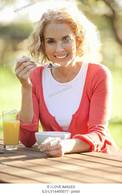 A mature woman sitting at a garden bench eating breakfast cereal