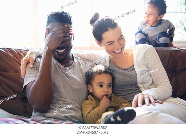 Laughing, happy multi-ethnic family on living room sofa