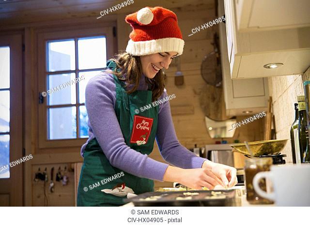Smiling teenage girl in Christmas Santa hat baking in kitchen