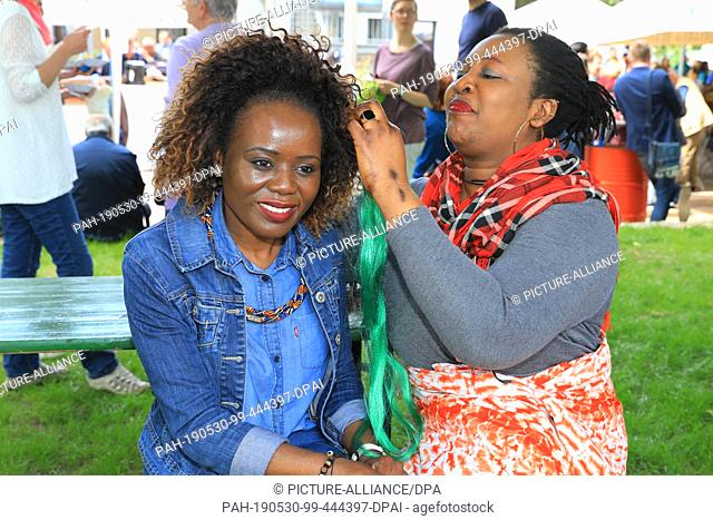 30 May 2019, Saxony-Anhalt, Magdeburg: Akue from Togo (r) and Geradine Muponda from Simbawe weave rasta plaits at the festival of encounter