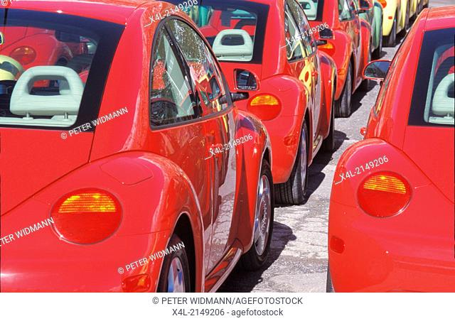 row of identic red cars brand VW Beetle