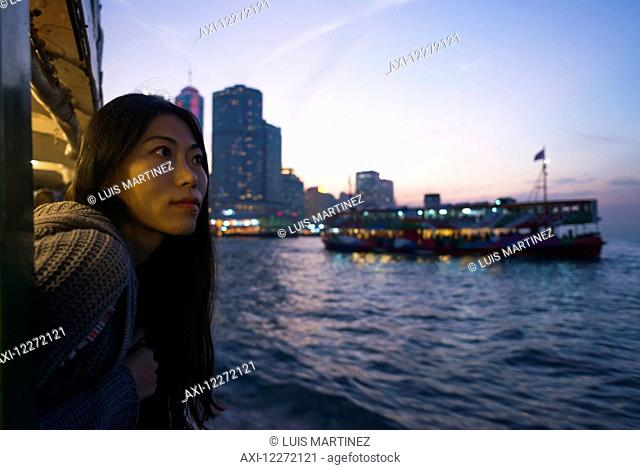 A young woman at the waterfront at sunset with a a boat and skyline in the background, Kowloon; Hong Kong, China