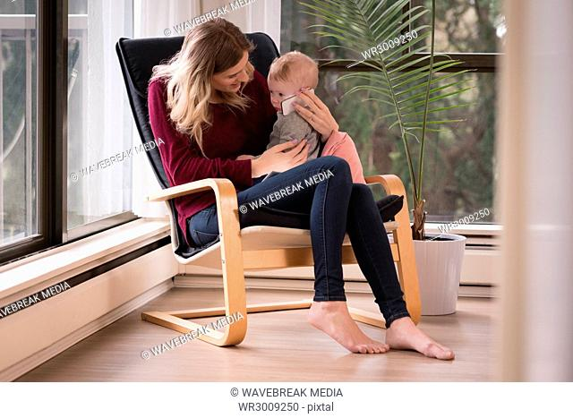 Mother holding phone on ear of boy while sitting on chair