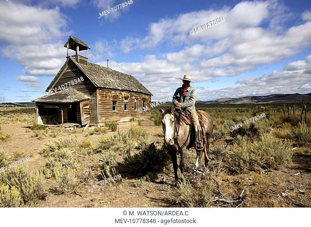 Cowboy on horse by old 1900's school building
