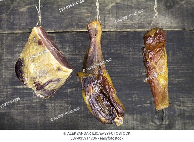 Smoked Pork and Chicken Meat Hanging on the Rope Against Wooden Background