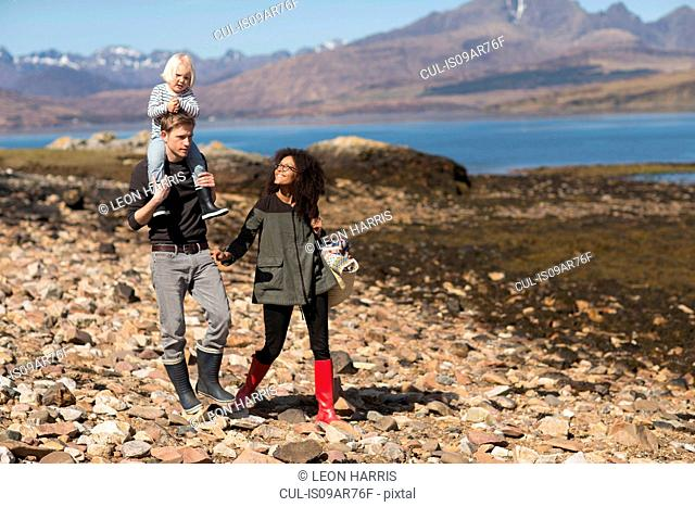 Family on walk, man carrying son on shoulders, Loch Eishort, Isle of Skye, Hebrides, Scotland