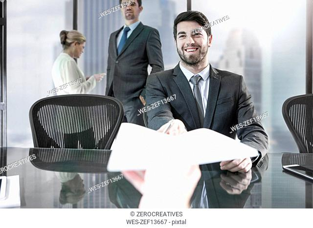 Businessman receiving paper in city office