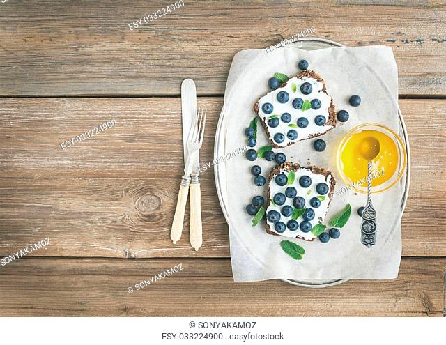 Healthy breakfast set with ricotta, fresh blueberries, honey and mint on a silver dish over a rustic wood background with a copy space
