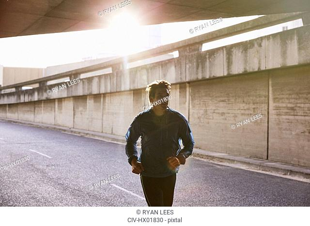 Male runner running into urban tunnel