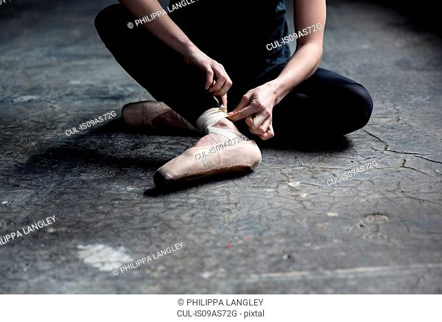 Dancer wearing ballet shoe in studio
