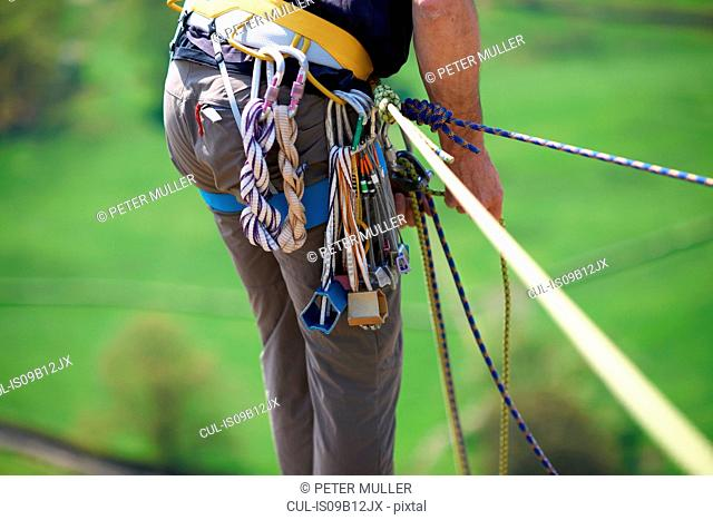 Cropped view of rock climber preparing climbing ropes on safety harness