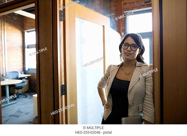 Portrait confident businesswoman in office doorway