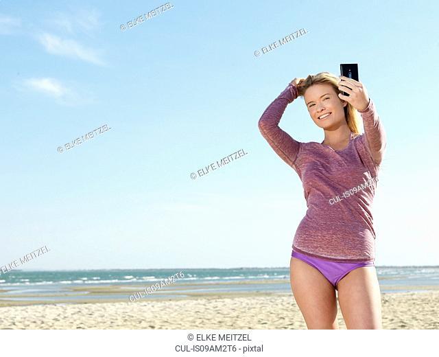 Young woman on beach posing for smartphone selfie, Altona, Melbourne, Victoria, Australia