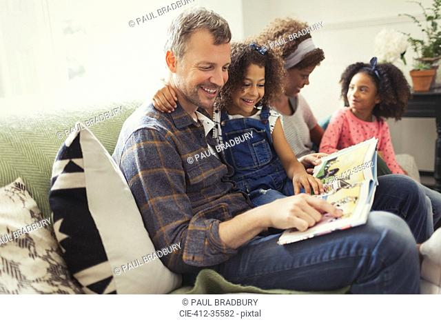 Smiling multi-ethnic father reading book with daughter on sofa