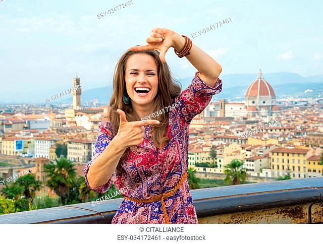 Happy young woman framing against panoramic view of florence, italy