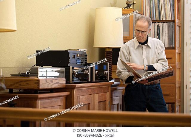 Senior man reading vinyl record cover in living room
