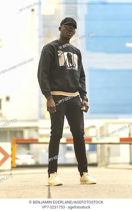 man wearing urban street style clothes, at industrial area in Munich, Germany