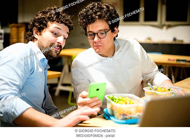 Colleagues in office using cell phone during lunch break