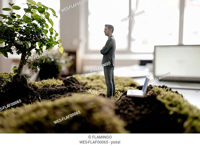 Businessman figurine with laptop standing on green moss