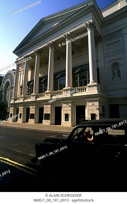 Car moving on a road in front of a building, Royal Opera House, Covent Garden, London, England