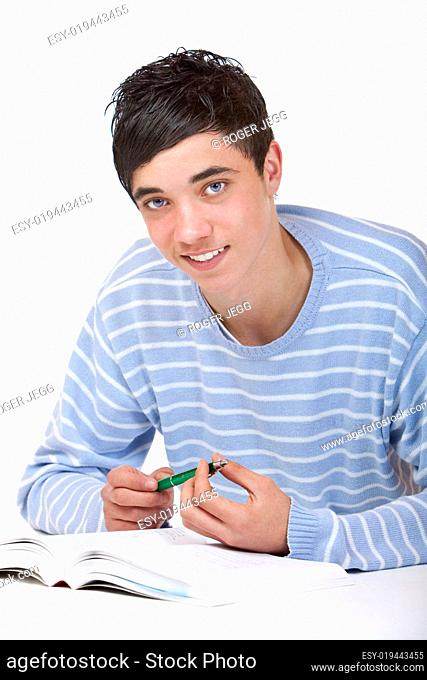 Young happy male student lying on floor learning from study book