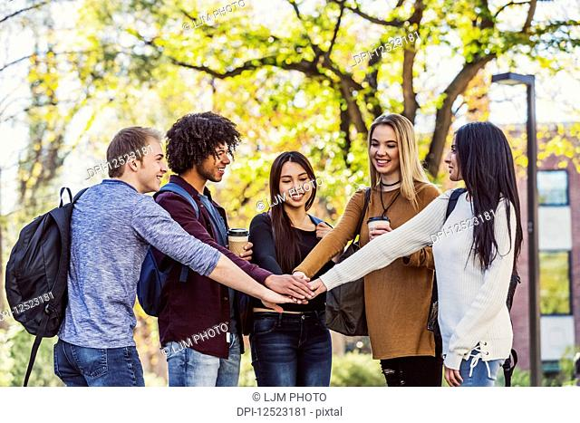 Five ethnically diverse student friends standing in a university campus with their hands on top each other's in agreememt that they are going to have a...