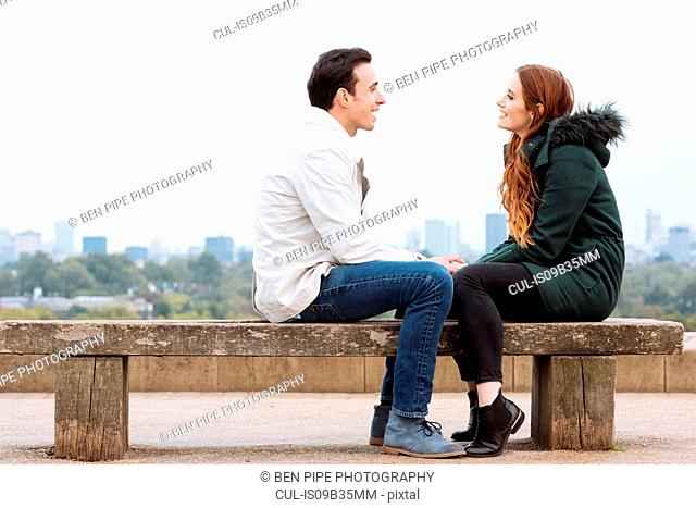 Side view of couple sitting face to face on bench
