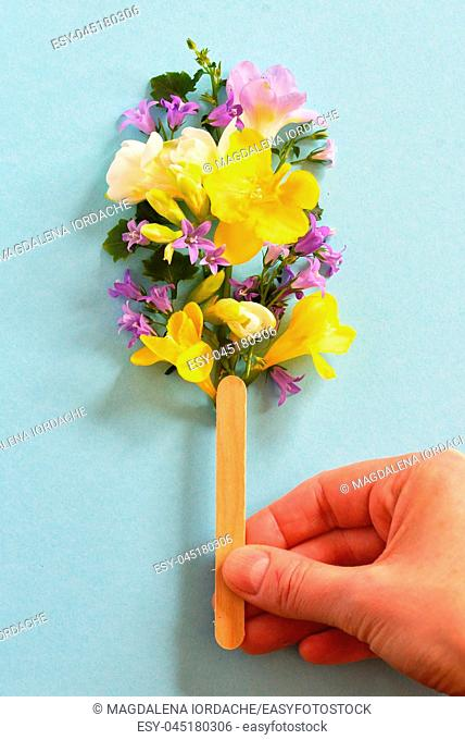 Concept hand holding popsicle from spring flowers