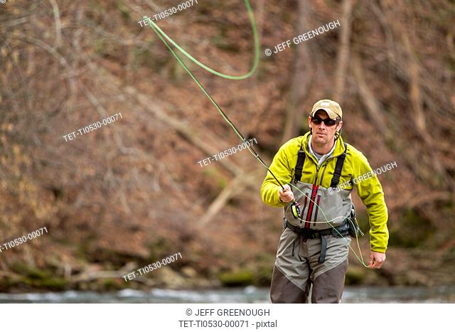 Young man fly-fishing in river