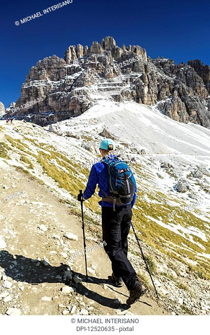 Female hiker on steep trail with rugged mountain peaks and blue sky in the background; Sesto, Bolzano, Italy